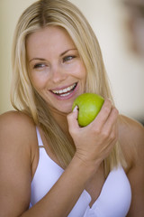 Young woman in underwear with apple, smiling, close-up