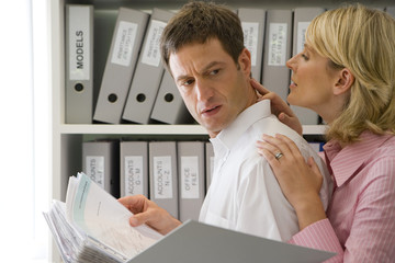 Businesswoman with hands on neck and shoulder of businessman with file by shelves, side view