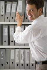 Young businessman taking file from shelf, smiling, portrait