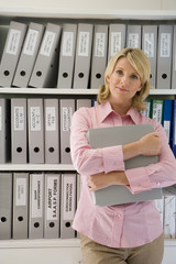 Businesswoman with file by shelves, smiling, portrait