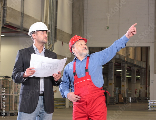 two workers in warehouse with papers
