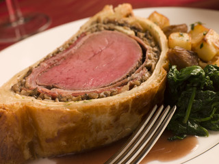 Slice of Beef Wellington with Spinach and Sauted Potatoes