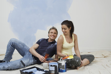 Couple resting by half-painted wall