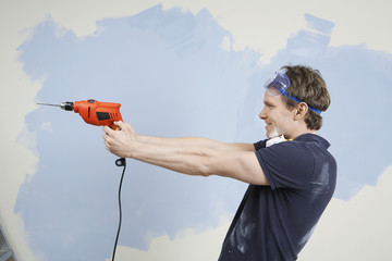 Man pointing drill in front of half painted wall, side view