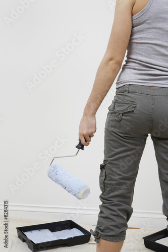 Woman holding paint roller by blank wall, mid section