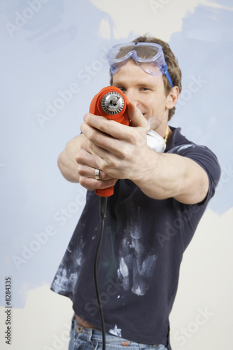 Man pointing drill in front of half painted wall, portrait