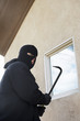 Burglar using crowbar to get into house