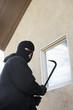 Burglar using crowbar to get into house