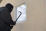 Burglar using crowbar to break into house