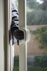Burglar breaking into house, close-up of hand