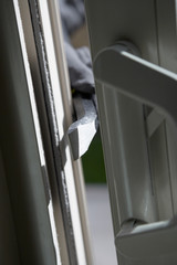 Burglar breaking into house, close-up of crowbar
