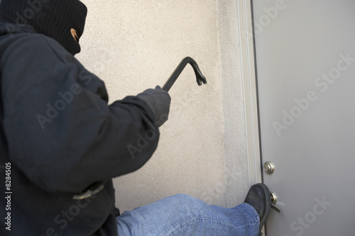 Burglar kicking door of house