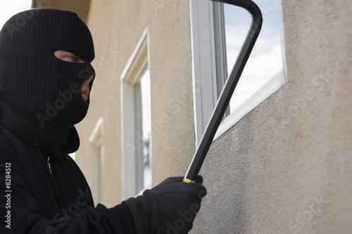 Burglar using crowbar to break into house