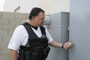 Security guard checking padlock