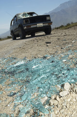 Close-up of broken windshield pieces on ground, truck in background
