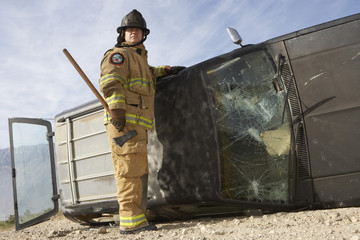 Firefighter standing by crashed car