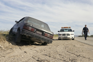 Police officer walking towards abandoned car on roadside