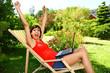 Frau im Liegestuhl mit Laptop ist Online Gewinner