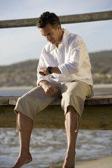 A man sitting on a boardwalk looking at his watch