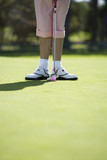 Woman playing golf, close-up of feet and putter