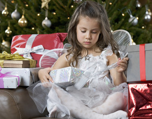 A young girl dressed as a fairy opening a Christmas present