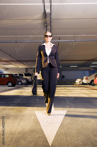 A businesswoman walking in a car park