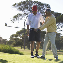 Young man receiving golf lessons