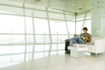 A man with a suitcase waiting in a lobby