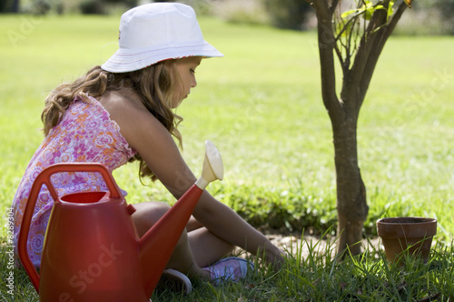 A young girl tending a plant in the garden