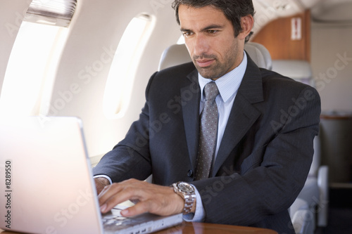 A businessman using a laptop in a plane