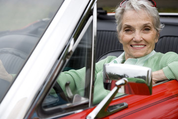 A senior woman driving a sports car
