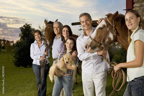 Three generation family portrait with horses and puppy