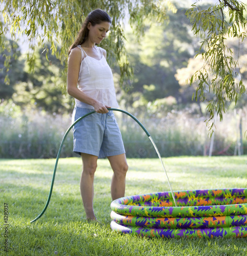 Mother filling a paddling pool with a garden hose