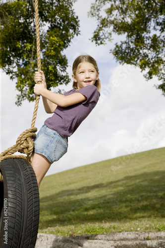 A young girl playing on a swing