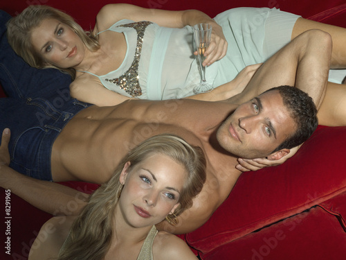 Portrait of a young man lying on couch with two young women