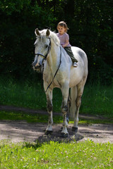 Beauty satisfied girl riding bareback by gray horse