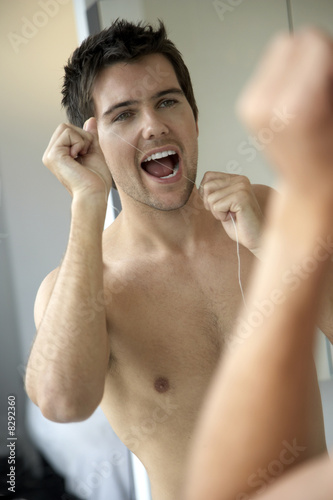 Young man flossing his teeth