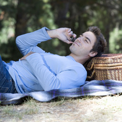A young man using a mobile phone at a picnic