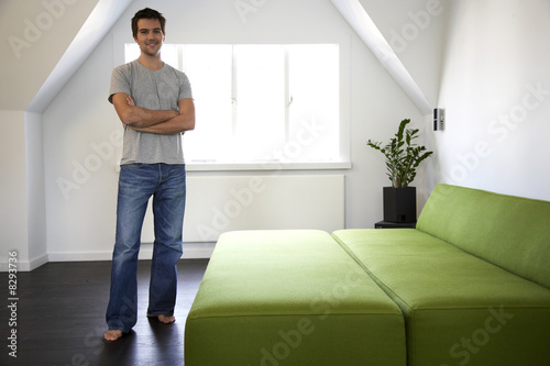 Young man standing in a bedroom
