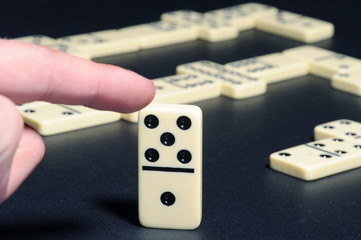 Human fingers push a dominoes.