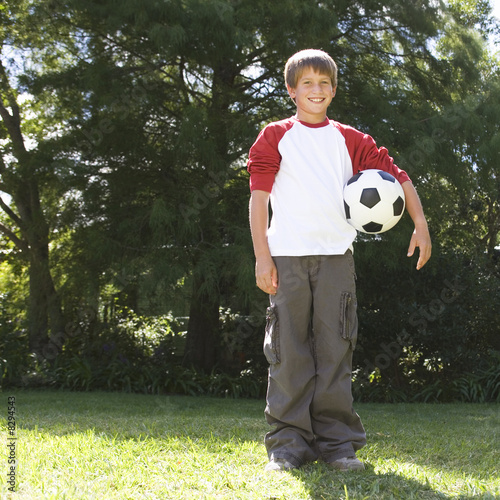 Young boy holding a football in a garden