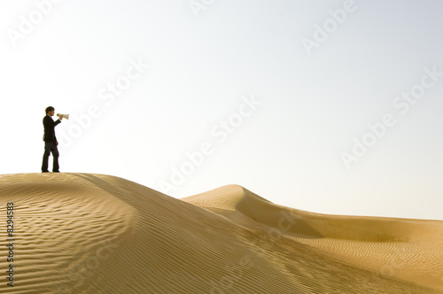 A young man standing in the desert with a loud hailer