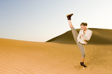 A young woman kick boxing in the desert