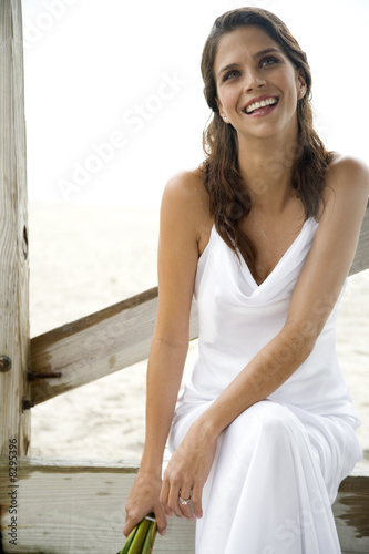 A bride sitting on a beach