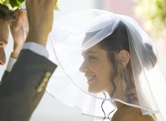 A groom lifting the veil of his bride