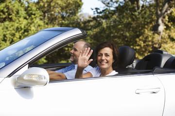 A senior couple driving a car