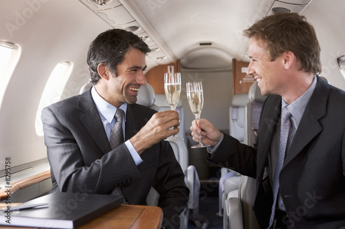 Two businessmen drinking champagne on a flight