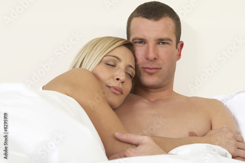 Young couple in bed, embracing