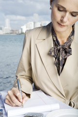 A businesswoman writing notes