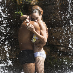 Young couple standing in a waterfall, embracing